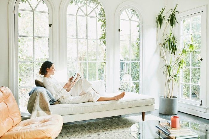 A woman reading on a white couch.