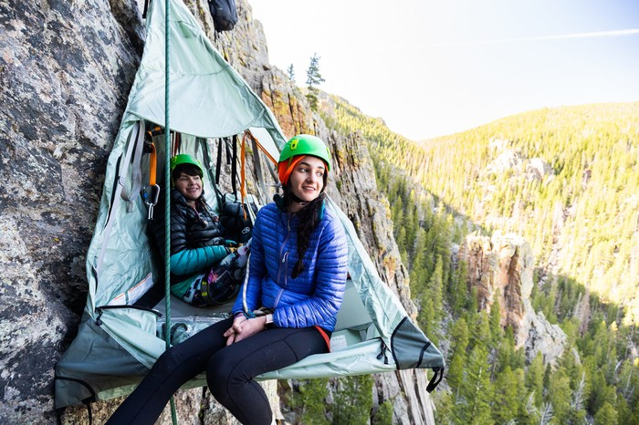 Two young people sit in a triangular tent on the side of a cliff.