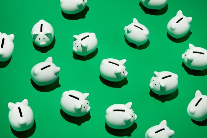A group of small white piggy banks against a green background.