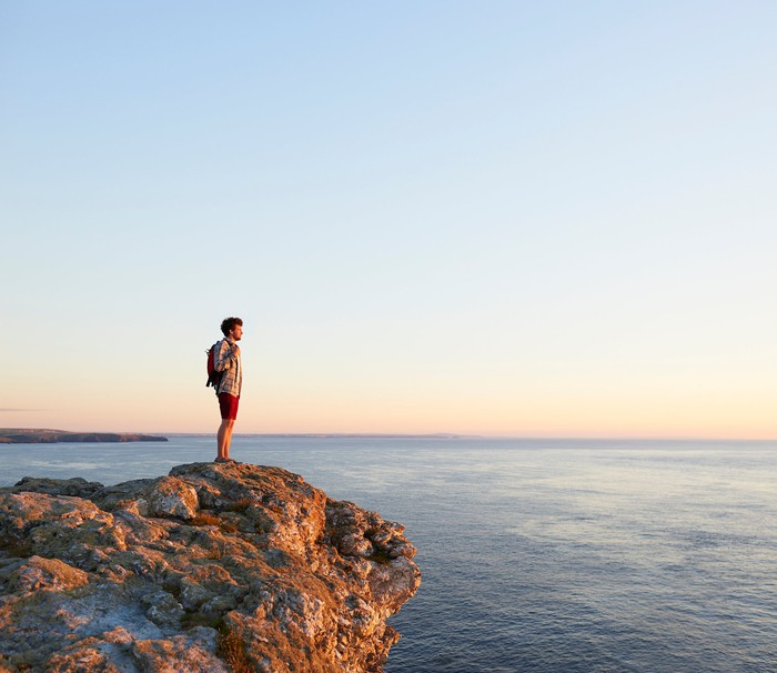 A man standing on a cliff overlooking the ocean