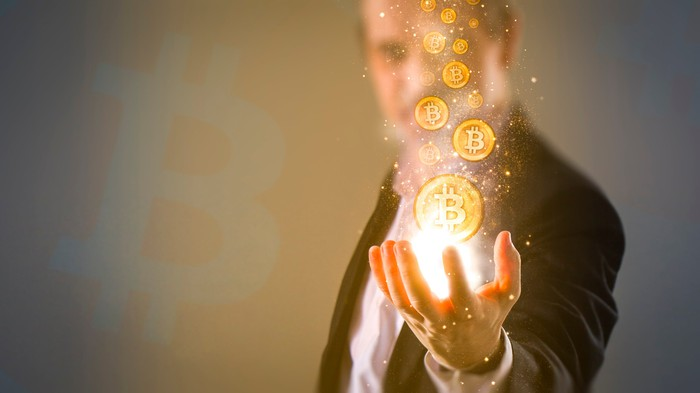 A man holding virtual Bitcoin tokens