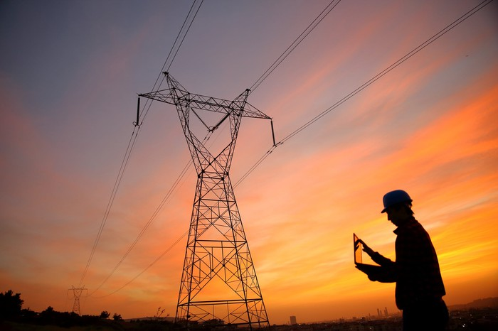 An engineer works in front of a high voltage tower at sunrise.