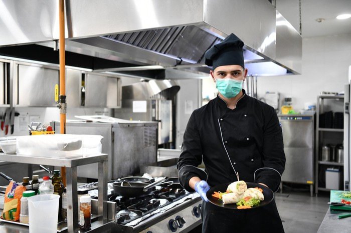 A chef wearing a medical mask holds a plate of food in a commercial kitchen.
