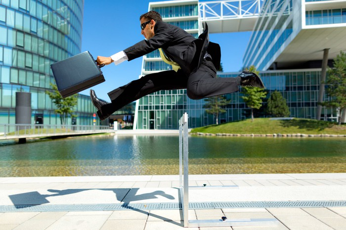 A businessman with a briefcase jumping across a hurdle, with a backdrop of modern buildings.