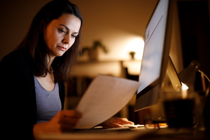 A woman looks from a computer screen to a printed piece of paper, doing research.