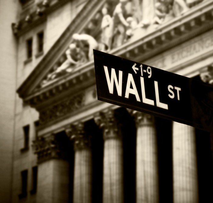 Wall Street sign, with New York Stock Exchange in background.