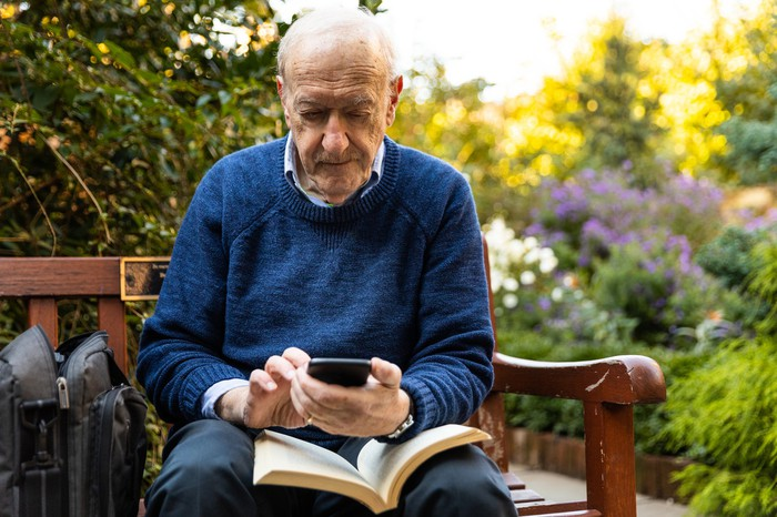Older man sitting on bench with book in lap holding phone