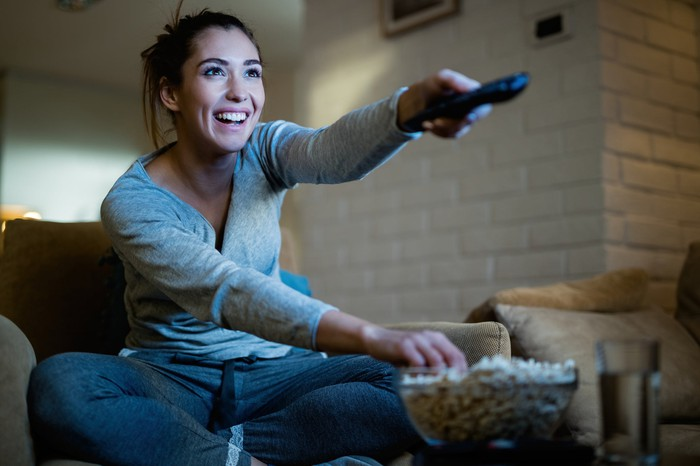 A delighted woman channel surfing with a remote as she reaches into her bowl of popcorn.