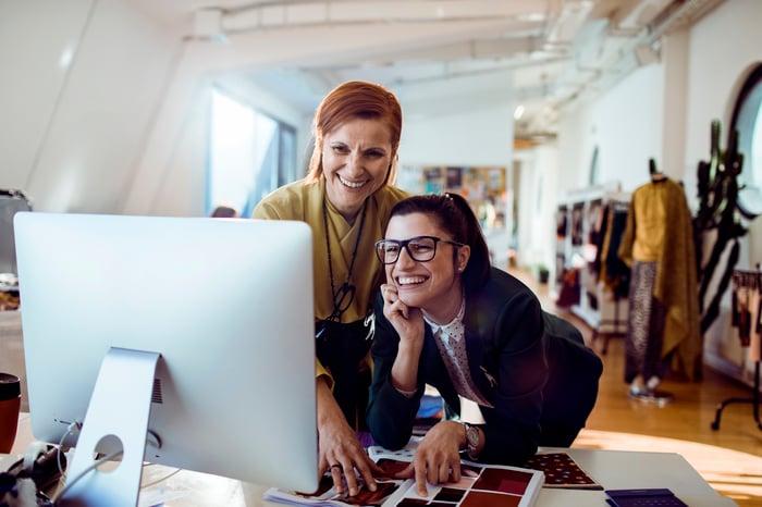 Deux femmes dans un studio de mode devant un ordinateur.