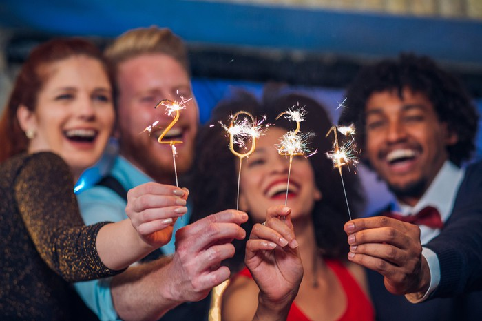 Two couples hold up sparklers to celebrate the start of 2021.