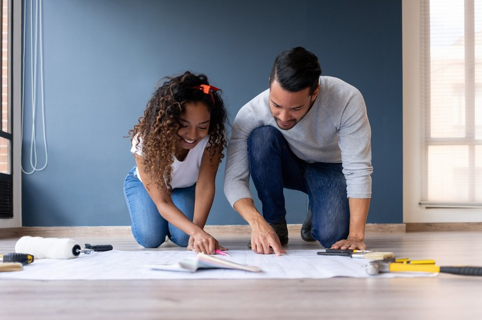 A man and woman working on a home improvement project.