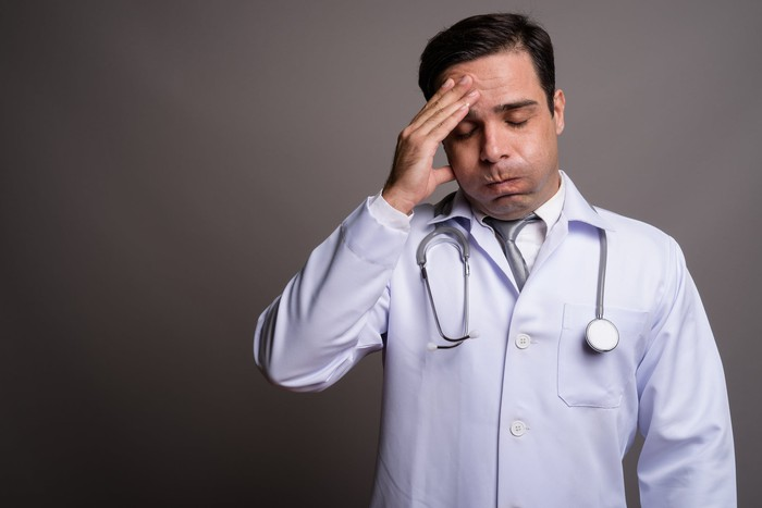 Doctor looking stressed with a hand on his forehead.