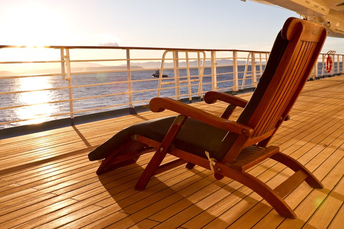 A lounge chair facing the sun on the deck of a cruise ship.