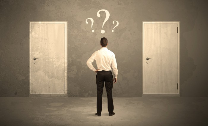 Man standing in front of two doors with three question marks over his head.