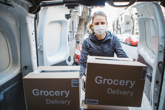 """A woman in a mask taking boxes labeled """"Grocery Delivery"""" out of the back of a sprinter van."""