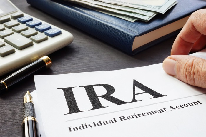 Document that says IRA on surface next to calculator, pen, and book with bills on it