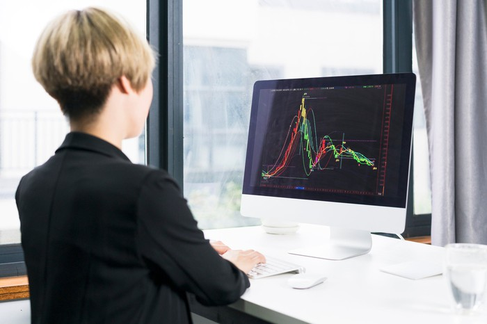 A woman looks at a stock chart that has a high peak and comes back down.