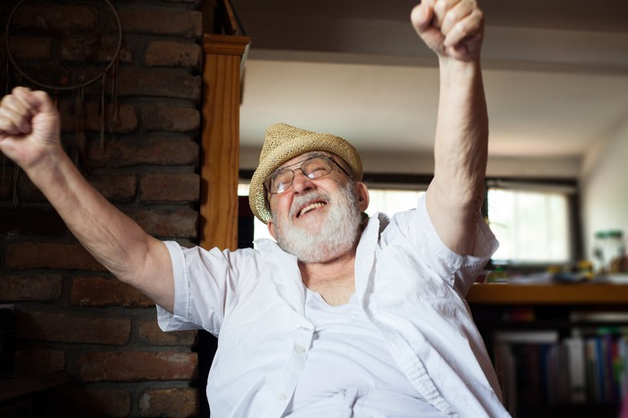 A happy older man is smiling, with arms outstretched.