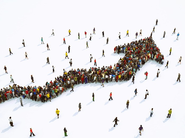 A crowd of people converging into a rising arrow.