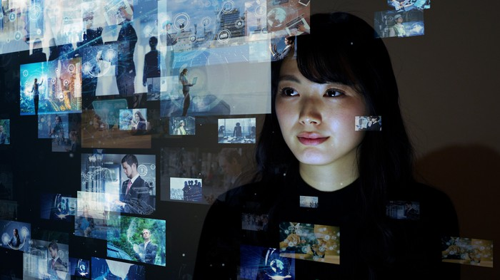 A woman looking at a glass wall with TV images on it