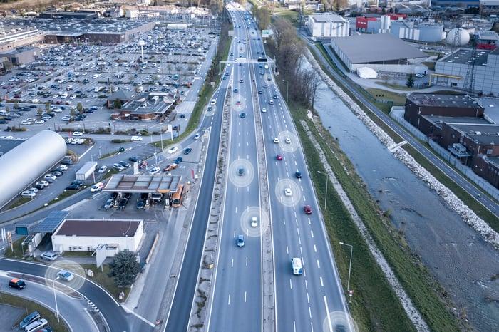 Autonomous vehicles driving down a highway.
