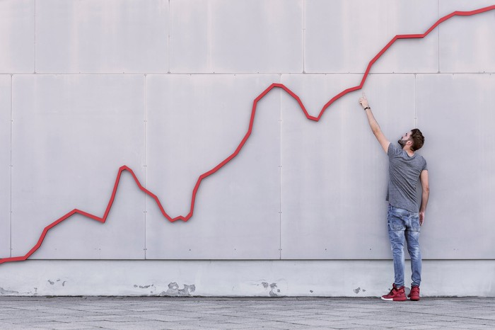 A man pointing to a rising trend line on a cement wall.