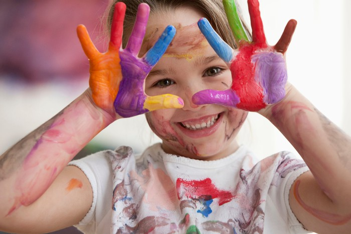 Child happily shows off her painted hands