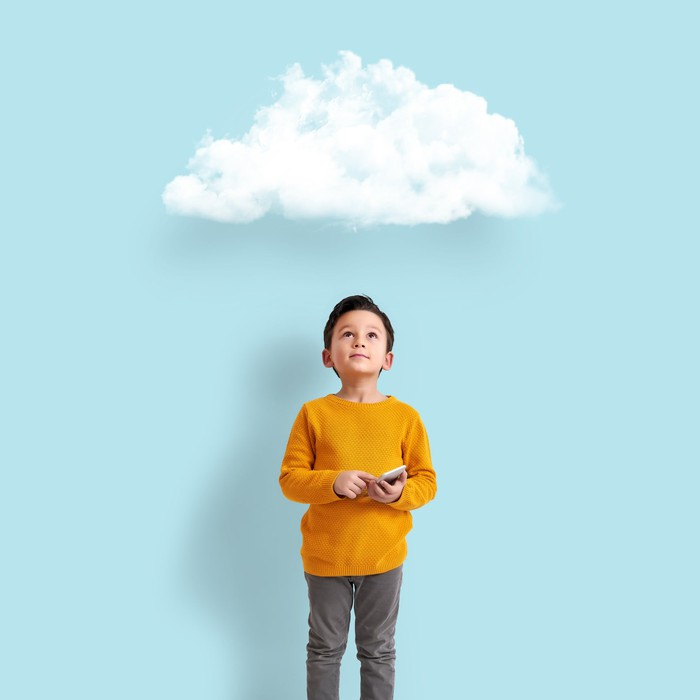 Little boy holding a device while staring at a cloud above him.