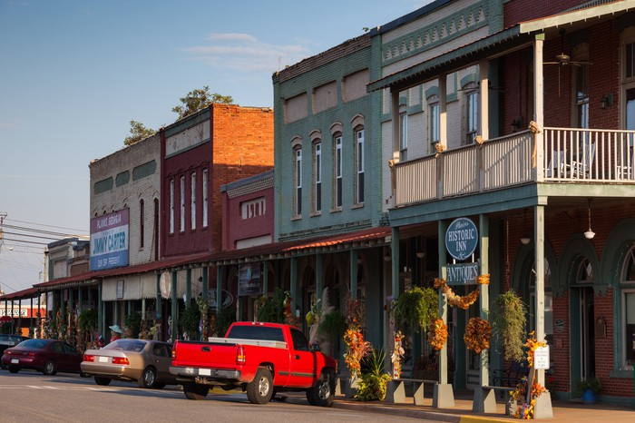 Main street in a small American town with stores, a red pickup truck, and several cars.