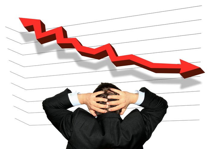 Person looking at a falling chart and holding his head in shock
