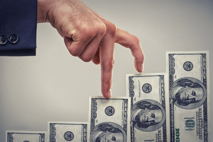 A man walking his fingers up a staircase of hundred dollar bills.