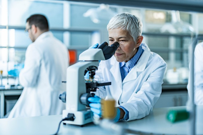 A scientist in a lab setting looks into a microscope.