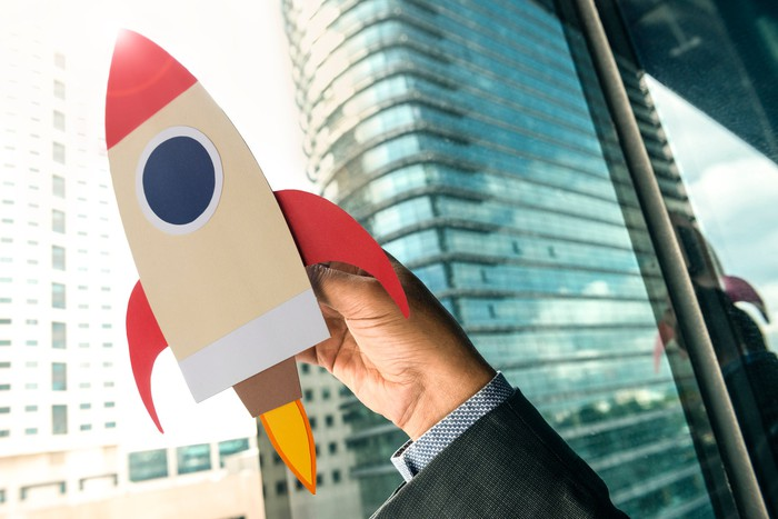 Hand holding a rocket cutout with buildings in the background