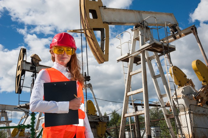 A woman in protective gear in front of oil wells.