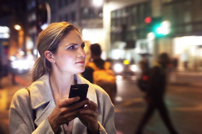A woman looking away in thought after looking at her smartphone on a city street.
