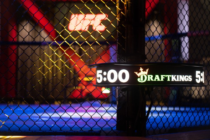 The DraftKings logo shown on the FightClock, with the ring and the UFC logo in the background.