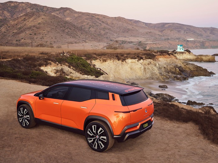 An orange Fisker Ocean electric SUV, parked by the ocean.