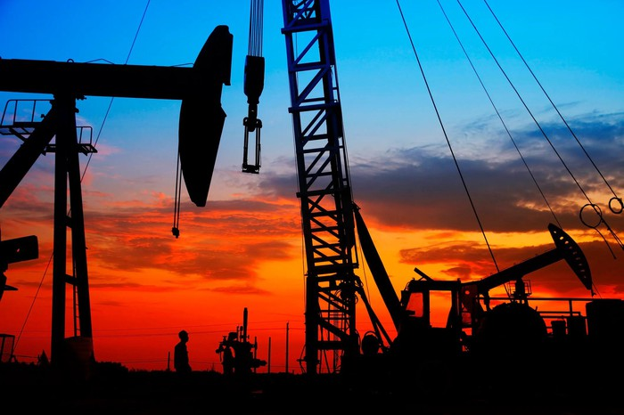 Crane, oil well, and drilling equipment near sunset.