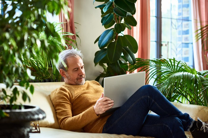 Senior man on couch looking at laptop