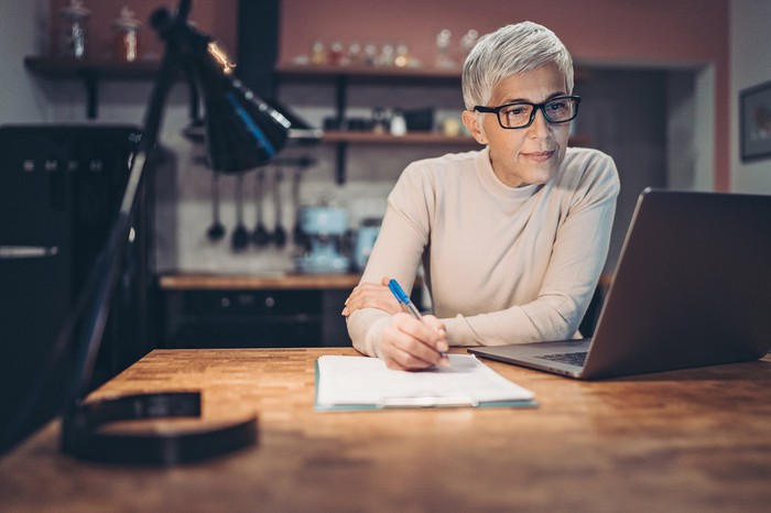 Senior woman checking her retirement account on laptop in her kitchen.