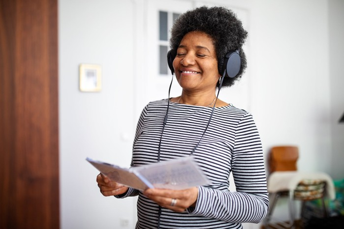 A standing woman listening to headphones with her eyes closed.