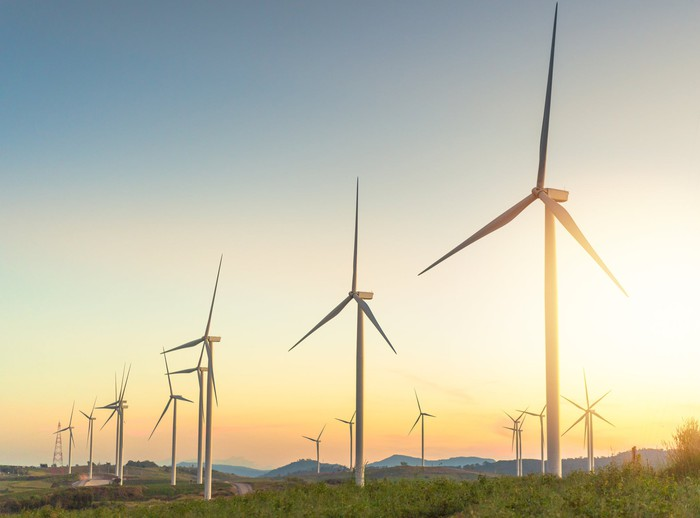 A row of wind turbines at dawn.