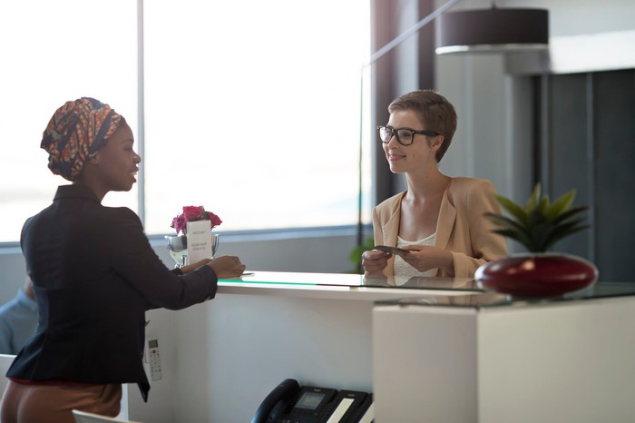 Woman talking to receptionist at a hotel reception desk.