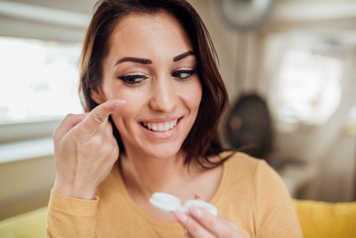Femme changeant de lentilles de contact.