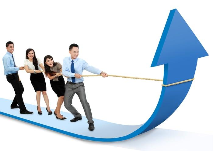 Un groupe d'hommes d'affaires debout sur une grande flèche travaille ensemble pour pointer la flèche vers le haut.