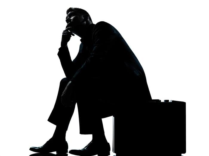 Silhouette d'un homme d'affaires assis dans une profonde réflexion sur sa mallette.