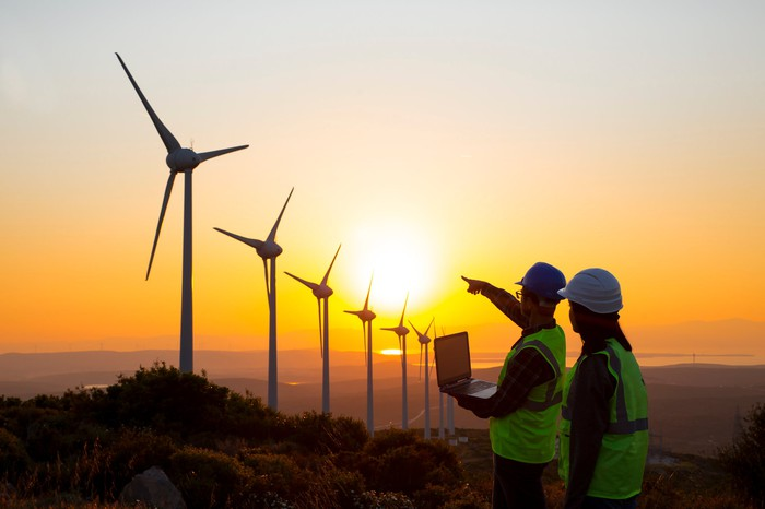 Two people in hard hats look at a row of wind turbines. One of the people is holding a laptop and pointing toward the turbines.