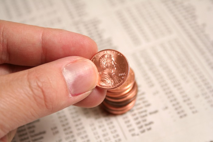 A hand holding a penny over a spreadsheet.