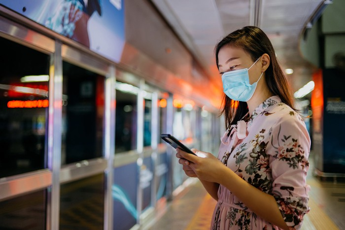 Young woman wearing a mask while using a smartphone in a public area.