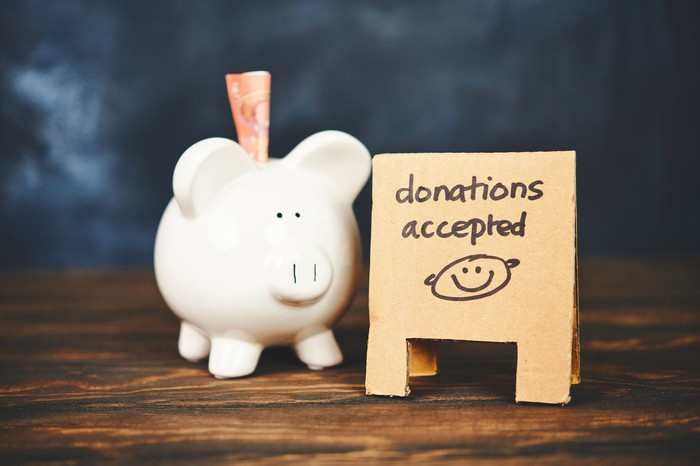 A piggy bank next to a sandwich board reading donations accepted.